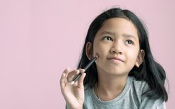 Asian girl holding a pencil and thinking something with pink background royalty free stock photo
