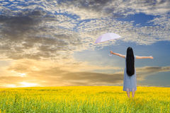 Asian girl holding pink umbrella in grass field Stock Photo