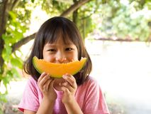 Asian girl holding slice orange melon on hands. Look like melon. Smiling. Fresh fruit royalty free stock images