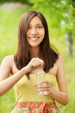Asian girl holding water bottle. Portrait of young  beautiful asian girl holding water bottle at summer green park Stock Photos