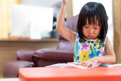 Asian girl home schooling sewing