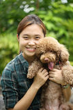 Asian girl hug with her poodle dog Royalty Free Stock Photography