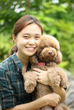 Asian girl hug with her poodle dog Stock Photos