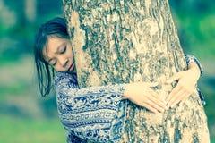 Asian girl hugging tree Stock Photo