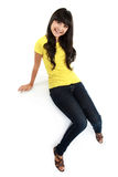 Asian girl in jeans sitting on the white table Stock Photo