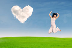 Asian girl jumping on green field Stock Images