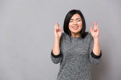 Asian girl keeping fingers crossed and eyes closed. Beautiful asian girl in gray jumper keeping fingers crossed and eyes closed Royalty Free Stock Photography