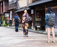 Kanazawa, Japan - September 29, 2015: Asian woman in colorful kimono posing for pictures in Higashi chaya historic geisha district stock images