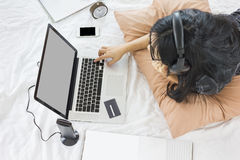 Asian girl lay down on bed surfing internet or shopping on website Royalty Free Stock Images