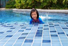 A girl learning to swim by the pool royalty free stock photography