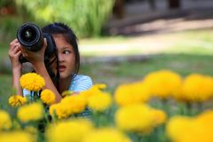 Asian girl learning to use dslr camera in the garden Royalty Free Stock Image