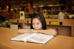 Asian girl in library. Asian girl reading book in library Royalty Free Stock Image