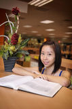 Asian girl in library. Asian girl reading book in library Stock Photos
