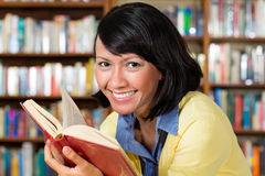Asian girl in library reading a book Stock Images