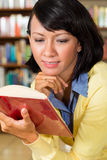 Asian girl in library reading a book Stock Photo