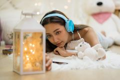 Asian girl listen music and relax in bedroom. Beatiful Asian woman in bedroom with many teddy bear toys look at fancy light bulb lamp while listen music from Stock Photo