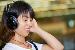 Asian girl listening to music on headphones Stock Photography