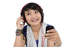 Asian girl listening to songs. From his cell phone, on white background Stock Photos