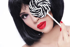 Asian girl with lollipop. Close-up portrait of young beautiful asian girl with red lipstick and fancy striped lollipop Stock Image