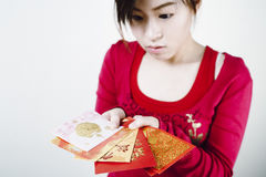 Asian girl look curious with Red packets. royalty free stock image