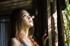 Asian girl look out with sunlight. Portrait of beautiful Asian girl look out from wooden window. Smiling brunette woman with light from outdoor with soft focus Stock Images