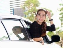 Asian girl looking at back of car Royalty Free Stock Photos