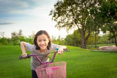 Asian girl looking at camera, smiling with a cute on bicycle in the outdoor park,child exercise in nature in the morning,healthy. Lifestyle concept stock image
