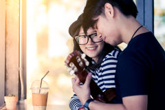 Asian girl looking at her boyfriend playing guitar with love royalty free stock images