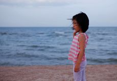 A lonely girl at the beach. A Asian girl looking lonely, waiting for someone at the beach stock image