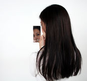 Asian girl looking in a mirror. An Asian girl looking in a mirror royalty free stock photo