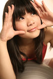 Asian girl looking up. With both hands on her face Stock Photo