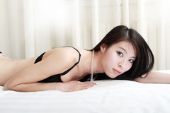 Asian girl lying on bed Stock Photos