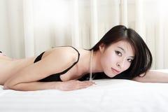 Asian girl lying on bed Stock Photos