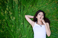 Asian girl lying on a meadow and yawn. Asian cute girl lying on a meadow and yawn Royalty Free Stock Photo