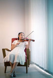 Asian girl lying on sofa in living room practice to playing viol. In with happiness emotion Stock Photos