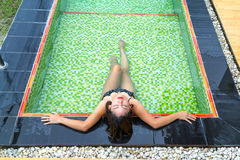 Asian girl lying in the swimming pool. Asian girl in black bikinis lying in the swimming pool with green mosaic tile Royalty Free Stock Photo