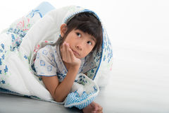 Asian girl lying under a blanket in the bed Stock Images