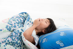 Asian girl lying under a blanket in the bed Stock Photos