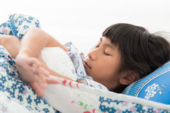 Asian girl lying under a blanket in the bed Royalty Free Stock Photography