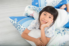 Asian girl lying under a blanket in the bed Stock Image