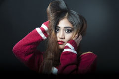 Asian girl. Girl with make-up, long hair, red pollover. Black beckground Royalty Free Stock Images
