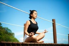 Asian girl meditating at the pier. Beautiful Asian girl relax and meditate at the pier Stock Photos