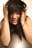 Asian girl with messy hair. Asian girl messes up her hair with both hands Stock Photos