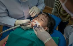Asian girl met the dentist for routine dental checkup and consult. Dental cleaning process royalty free stock photography