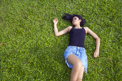 Asian girl with mini skirt. Sexy erotic asian girl with mini skirt on green grass Royalty Free Stock Image
