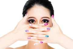 Asian girl model hands cross covered mouth. Showing painting finger nails and colorful eyes focusing isolated on white wall background Royalty Free Stock Image