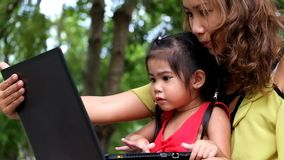 An asian girl and mother are using notebook comput. Er stock video