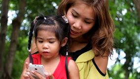 An asian girl and mother are using smart phone. stock footage