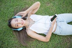 Asian girl music lover top view. Flat lay or top view portrait of Smile beautiful Asian woman listen music  on grass in park. Happy brunette girl wear headphone Royalty Free Stock Image