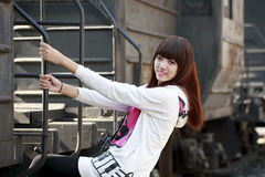 Asian girl next to train. Asian girl posing next to abandoned train caboose Royalty Free Stock Photos